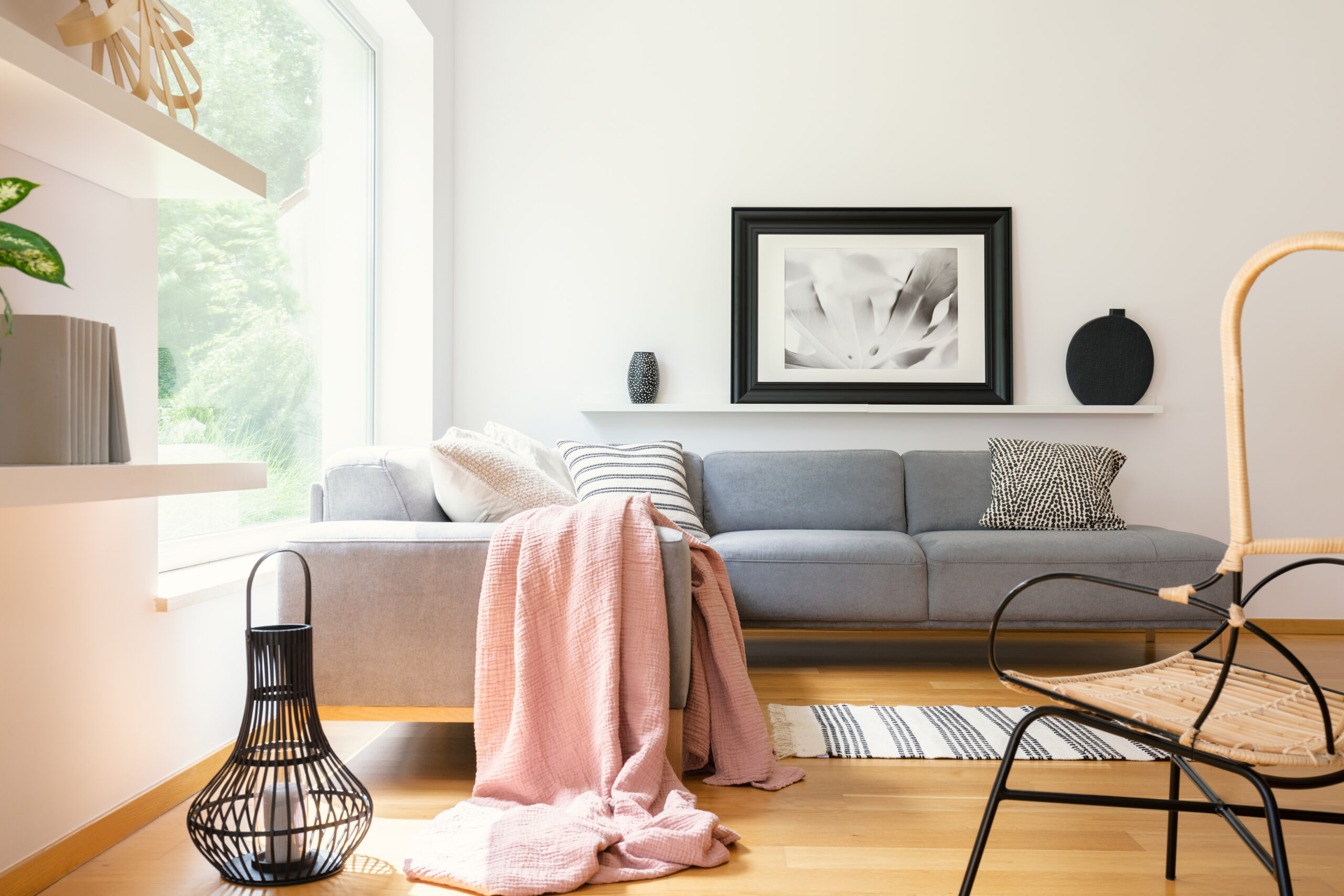 Pastel pink blanket thrown on corner couch standing in white living room interior with simple poster, lantern, decor and big window in the real photo